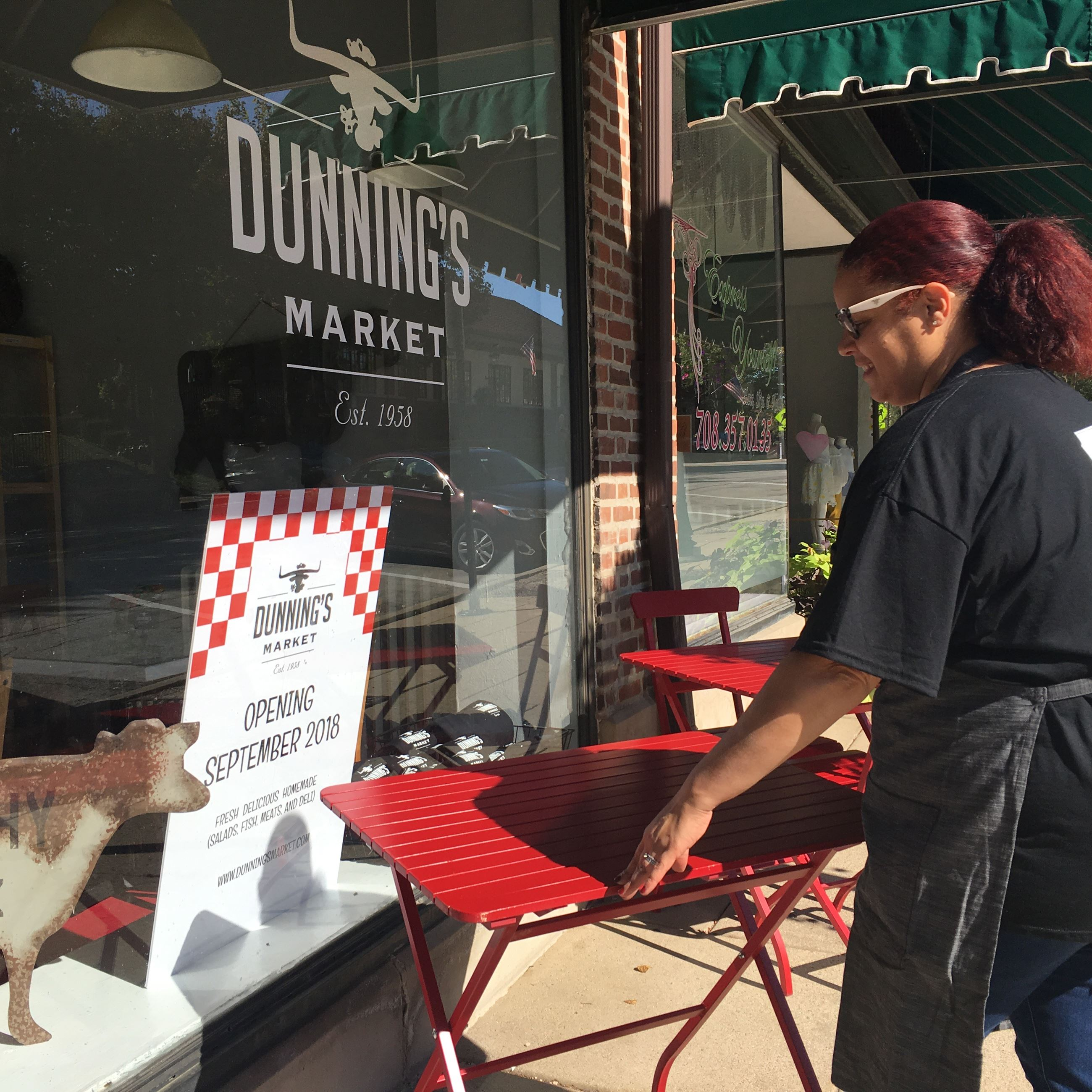 Woman Setting Up Tables Outside Dunning's Market
