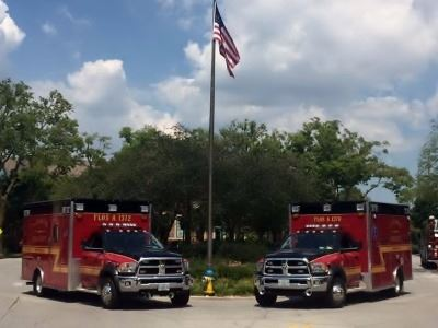 Two Ambulances Parked by a Flagpole